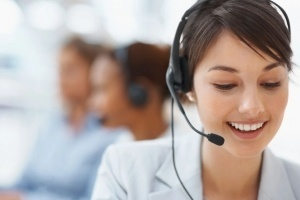 This picture shows a lady smiling while helping a customer with Computer Repair and Network Support