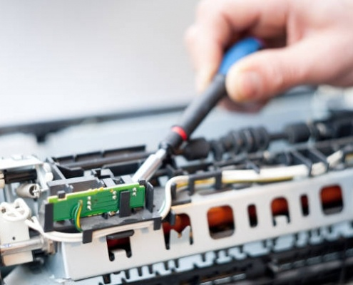 This is a picture of a laser printer repair man hands fixing a laser printer
