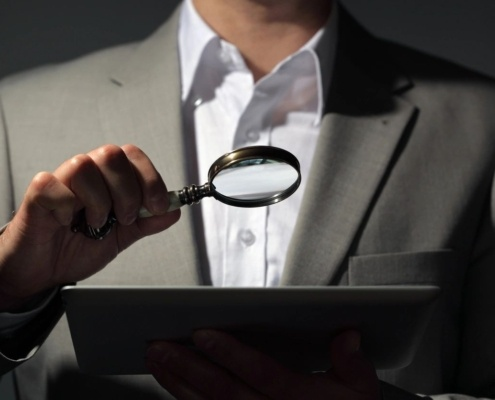 photo of man performing an investigation using a magnifying glass